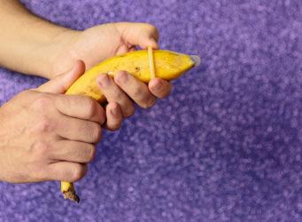 una mano pone un preservativo a una banana