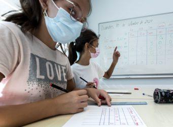 dos niñas con mascarilla estudian en una mesa