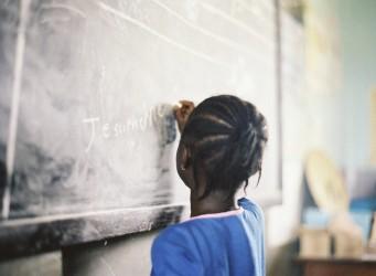 una joven de color de espaldas escribiendo en una pizarra