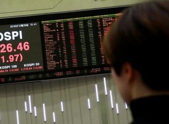 una joven mirando un rótulo en la Bolsa de Seúl