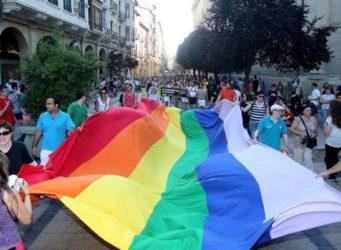 Personas portando una gran bandera arcoiris