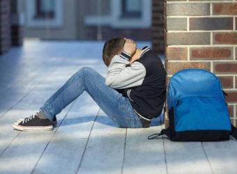 imagen de un joven sentado en el suelo con aspecto de agobiado