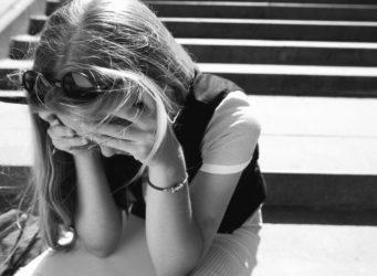 Una joven que se cubre la cara con las manos