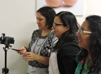 tres mujeres preparando una cámara de fotos