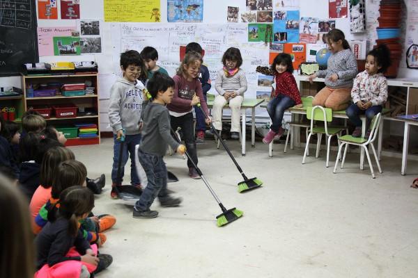 niños y niñas barriendo la clase