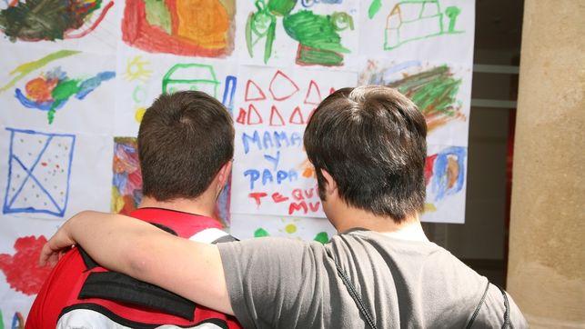 imagen de un joven que pasa su brazo por los hombres de otro joven que parece tener síndrome de Down