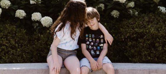 una niña le da un beso a un niño sentados en un banco