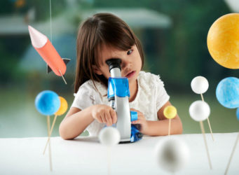 imagen de una niña mirando por un microscopio