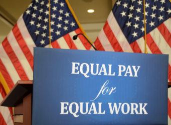 Imagen del cartel igual paga por igual trabajo en inglés delante de la bandera de USA