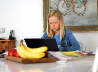 una niña trabaja en una casa con un ordenador