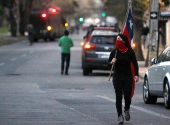 una mujer chilena con la cara tapada y una bandera