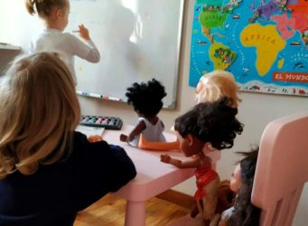 niñas en una escuela jugando con muñecas