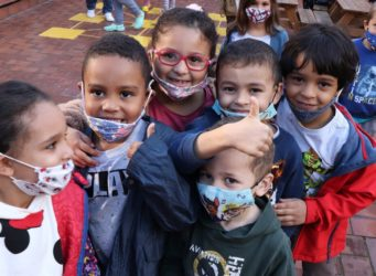 un grupo de niños y niñas en una clase con mascarillas