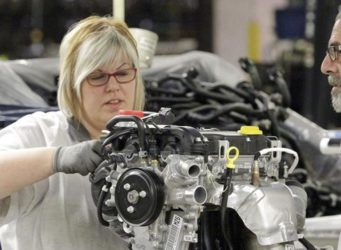 dos trabajadores, hombre y mujer, trabajan en una pieza de maquinaria