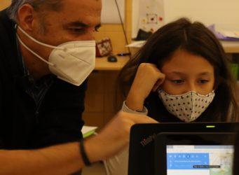 una niña y un adulto con mascarillas miran pantallas