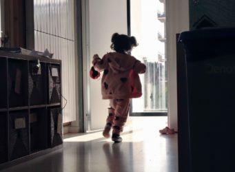 una niña ante una ventana con una mascarilla en la mano