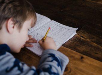 un niño escribe en un cuadernillo