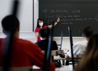 una profesora ante una pizarra con fórmulas
