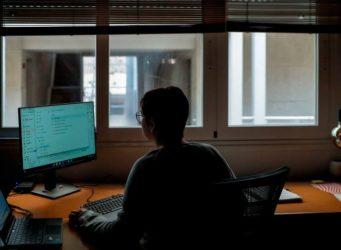 mujer ante un ordenador y ventana