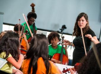 grupo de niños y niñas con instrumentos musicales y una profesora