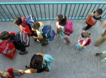 niñas y niños entrando en un colegio